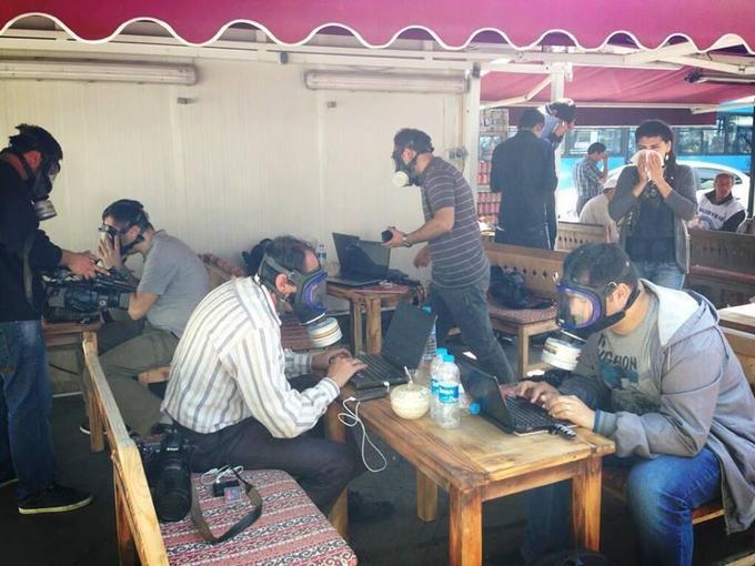 Turkish journalists wearing gasmasks while working on their laptops